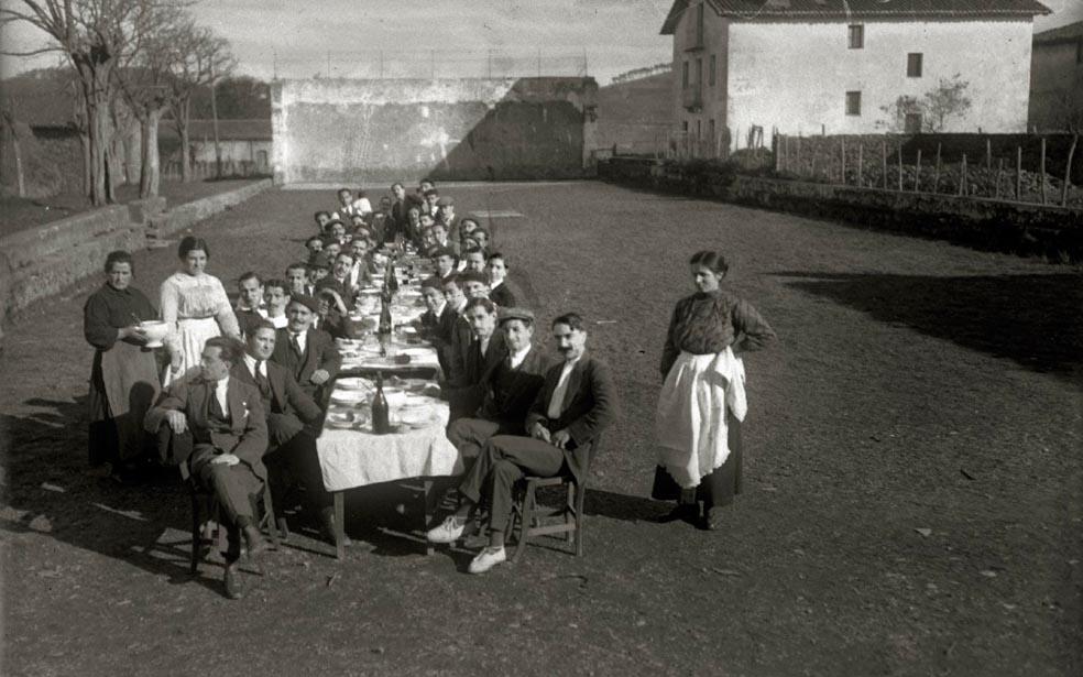 Hainbat pertsona Zubietako frontoian, bazkari herrikoi batean, 1916an. (Argazkia: Martin Ricardo / Kutxa Fototeka)